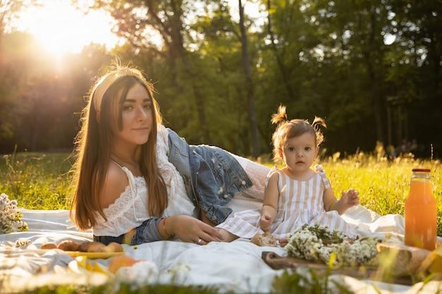 Een jonge moeder en haar dochtertje picknicken in een stadspark.