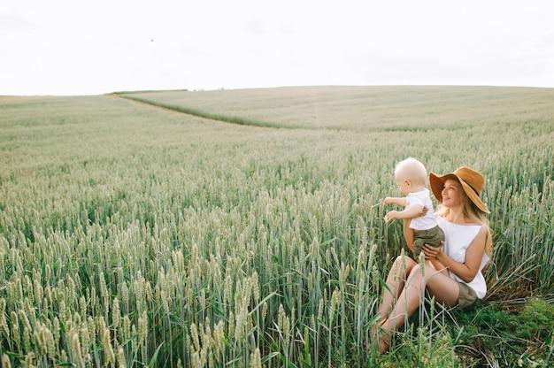 Een jonge moeder en haar klein kind zitten in de buurt van de tarwe op een groene achtergrond
