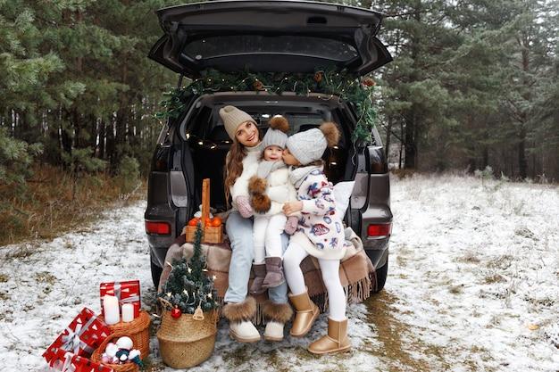 Een jonge moeder en twee kleine meisjes zitten in de kofferbak van een auto