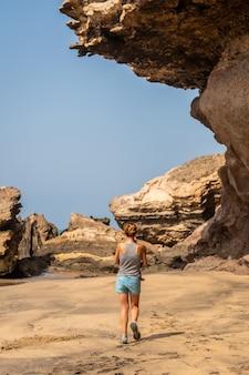 Een jonge moeder geniet van een vakantie aan zee in playa de garcey, westkust van fuerteventura, canarische eilanden. spanje