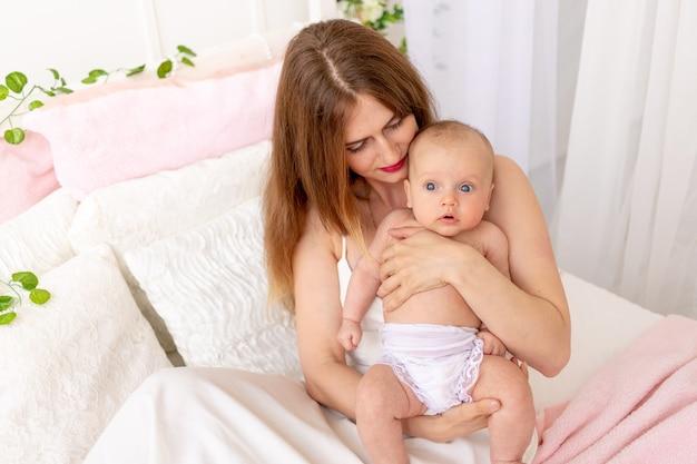 Een jonge moeder houdt een kind in haar armen en bewondert het in een prachtig interieur