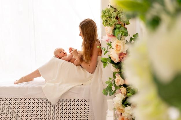 Een jonge moeder houdt een kind in haar armen en bewondert het zittend op het raam