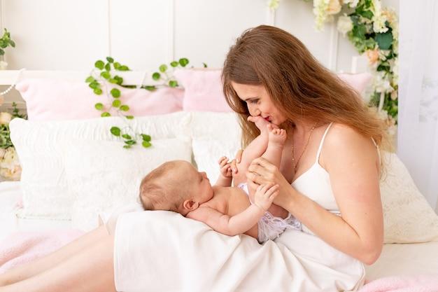 Een jonge moeder houdt een kind in haar armen en kust zijn benen in een prachtig interieur
