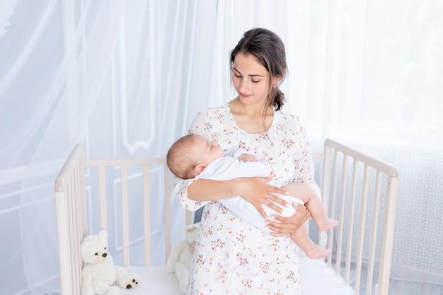 Een jonge moeder houdt een pasgeboren baby in haar armen en laat hem slapen in de slaapkamer bij de wieg, het concept van moederschap en een gelukkig gezin.