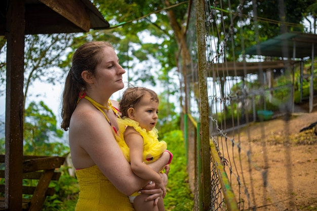 Een jonge moeder houdt een schattige peuter in haar armen en kijkt over het hekwerk in de dierentuin