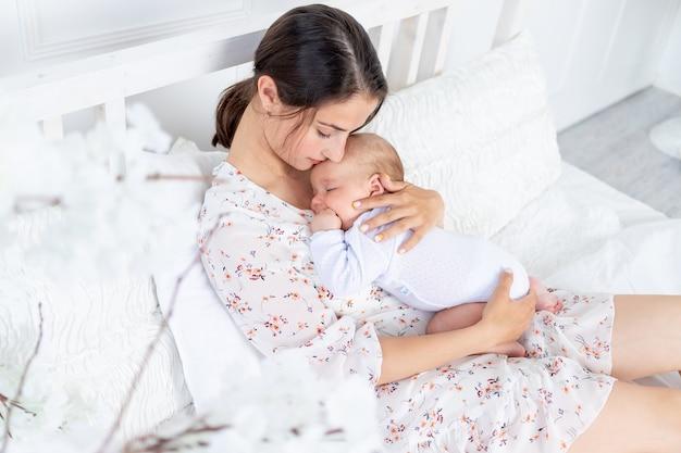 Een jonge moeder houdt een slapende pasgeboren baby in haar armen op het bed in de slaapkamer, het concept van moederschap en een gelukkig gezin