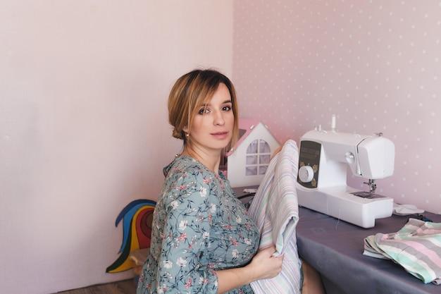 Een jonge moeder houdt zich in haar vrije tijd thuis bezig met haar favoriete hobby