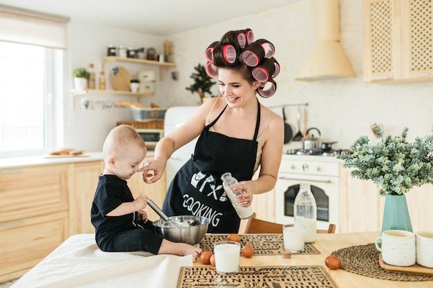 Een jonge moeder in een schort en krulspelden bereidt een verjaardagstaart in de keuken met haar kleine kind