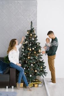 Een jonge moeder in een witte trui en een spijkerbroek zit op de bank bij de kerstboom en versiert het met speelgoed, vader met een baby in zijn armen staat naast en versiert ook de kerstboom