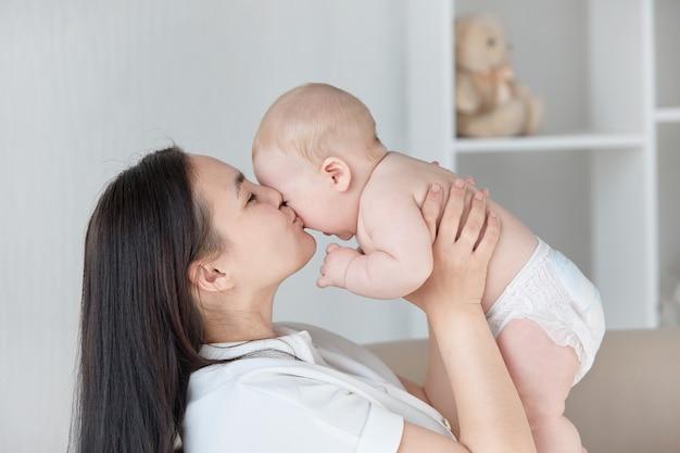 Een jonge moeder kust een lachend kind in een lichte kamer, een plek om tekst te kopiëren