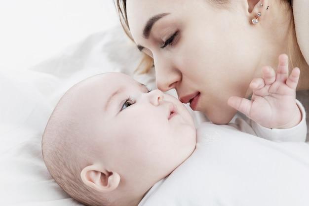 Een jonge moeder kust een pasgeboren baby. liefde en tederheid. detailopname.