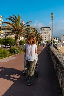 Een jonge moeder loopt haar zoon in de auto in de zomer op de grande plage in saint jean de luz, vakantie in het zuiden van frankrijk, frans baskenland