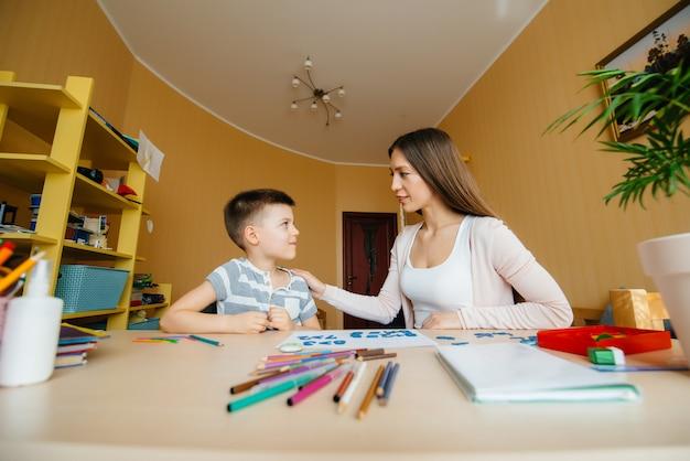 Een jonge moeder maakt huiswerk met haar sonthuis. ouders en training.