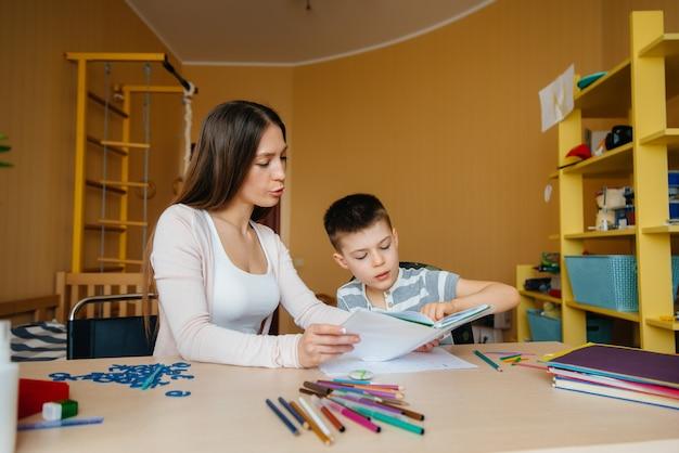 Een jonge moeder maakt thuis huiswerk met haar zoon. ouders en training.