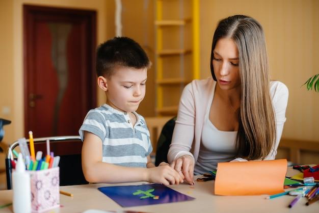 Een jonge moeder maakt thuis huiswerk met haar zoon