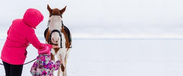 Een jonge moeder met dochtertje in felgekleurde winterkleren voedt een wit en bruin paard