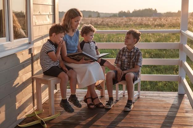 Een jonge moeder met drie kinderen leest een boek op de zomerveranda