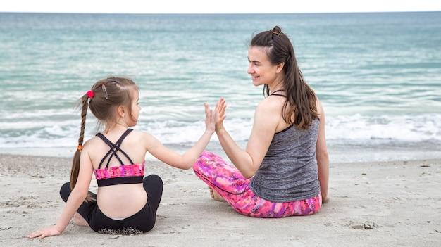 Een jonge moeder met een dochtertje in sportkleding zit op het strand tegen de achtergrond van de zee. familiewaarden en een gezonde levensstijl.