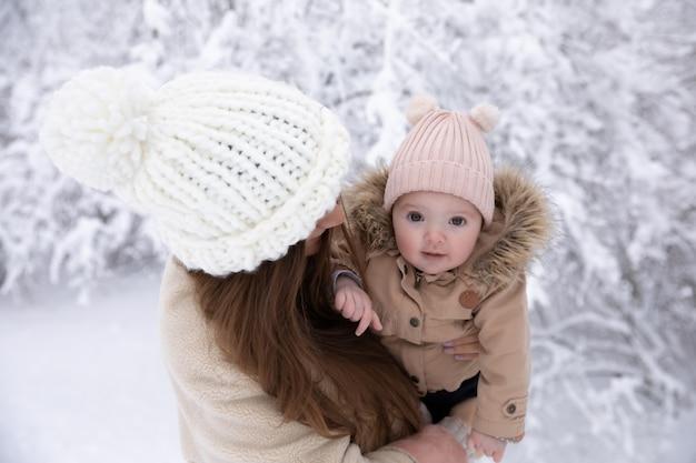 Een jonge moeder met een klein kind speelt in de sneeuw