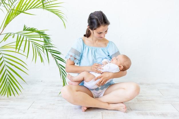 Een jonge moeder met een pasgeboren baby houdt het zachtjes in haar armen, knuffelt en bewondert het thuis, het concept van een gelukkig gezin en de geboorte van kinderen.