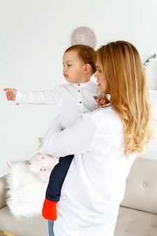 Een jonge moeder met een schattig zoontje vermaakt zich in een lichte, gezellige woonkamer