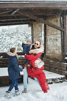 Een jonge moeder met haar drie kinderen vermaakt zich met sneeuwballen en speelt buiten in de buurt van het huis. nieuwjaar concept