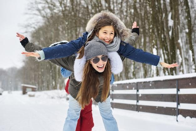Een jonge moeder met haar kinderen die plezier hebben in de winter