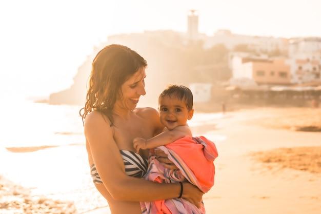 Een jonge moeder met haar zes maanden oude baby geniet van een zonsondergang op een strand, morro jable, gemeente pajara ten zuiden van fuerteventura, canarische eilanden. spanje