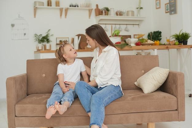 Een jonge moeder praat van hart tot hart met haar kind. de psycholoog communiceert met een klein meisje thuis.