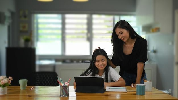 Een jonge moeder staat en begeleidt haar dochter bij het houten studentenbureau door computertablet.
