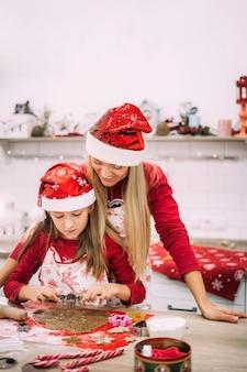 Een jonge moeder staat in de keuken naast haar dochter en kijkt toe