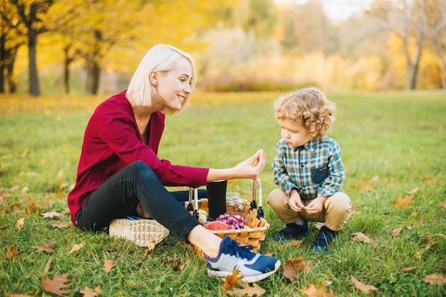 Een jonge moeder voedt haar kleine baby in het park met fruit.
