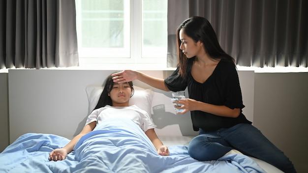 Een jonge moeder zorgt voor haar zieke dochter in de slaapkamer.