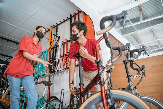 Een jonge monteur die de zadelpen bevestigt en een verkoopster met masker controleren een nieuwe fietsonderdelen voor de klant