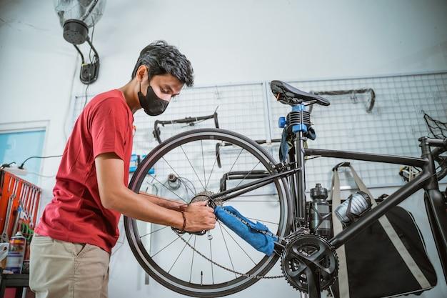 Een jonge monteur met masker aan het werk om de fietsas vast te draaien