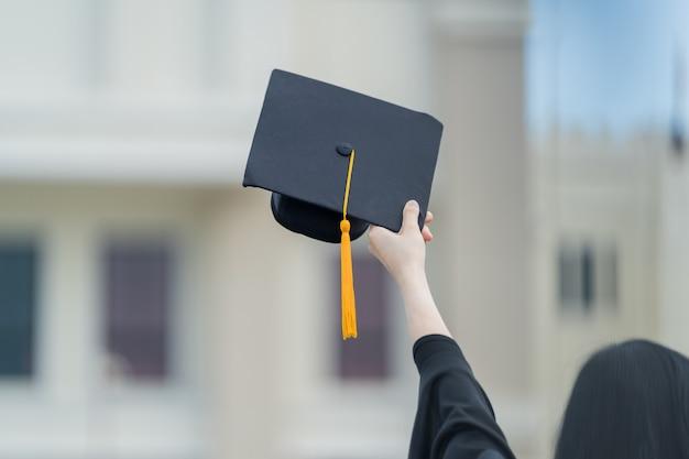 Een jonge, mooie aziatische vrouw afgestudeerd aan de universiteit in afstudeerjurk en baret houdt een diploma voor het universiteitsgebouw na deelname aan het begin van de universiteit