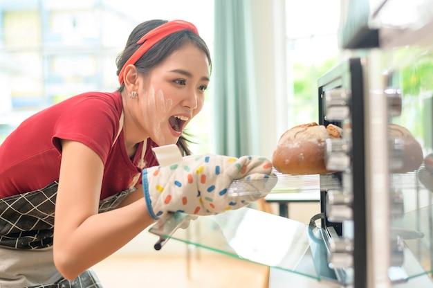 Een jonge, mooie aziatische vrouw bakt in haar keuken-, bakkerij- en koffiewinkelbedrijf