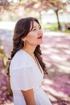 Een jonge mooie aziatische vrouw in een witte jurk loopt in een bloemrijk park. sakura. bloeiende bomen. voorjaar.