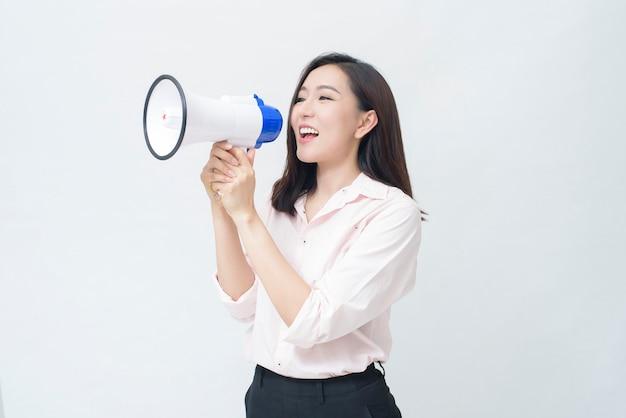 Een jonge mooie aziatische vrouw kondigt door megafoon op witte achtergrond aan