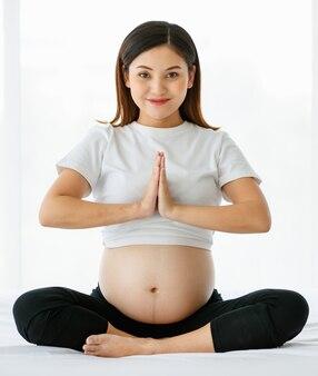 Een jonge mooie aziatische vrouw zittend op een bed sluit zich aan bij haar handen voor haar borst met een smiley die naar een camera kijkt. yoga is een geweldige oefening voor zwangere dames.