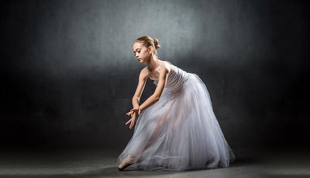 Een jonge mooie ballerina poseert in de studio. een kleine danser. ballet.