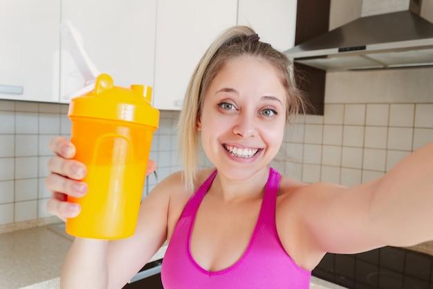 Een jonge mooie blanke blonde vrouw houdt een eiwitshake in een oranje shaker en neemt een selfie