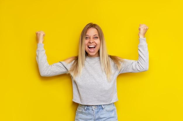 Een jonge, mooie blanke onder de indruk opgewonden lachende blonde vrouw met armen omhoog in een vrijetijdskleding is blij met het nieuws of de loterijwinst geïsoleerd op een felle gele muur