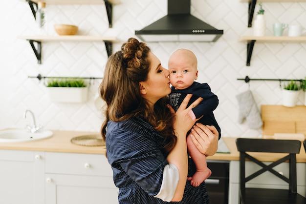 Een jonge mooie blanke vrouw zit aan de keukentafel en kust haar lieve kleine baby