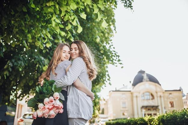 Een jonge mooie blonde dochter omhelst haar moeder van middelbare leeftijd in de straten van de stad.