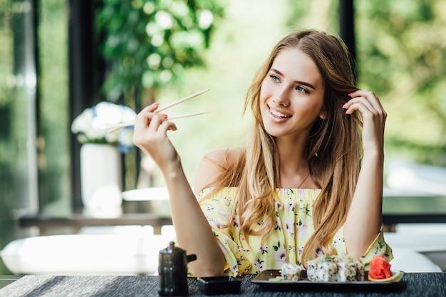 Een jonge, mooie blonde, mooie vrouw die sushi eet op het zomerterras van een japans restaurant