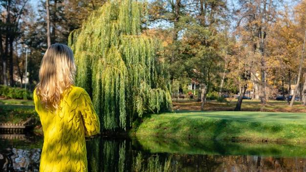 Een jonge mooie blonde vrouw die door het de herfstpark loopt en zich in kleurrijke boombladeren verheugt.