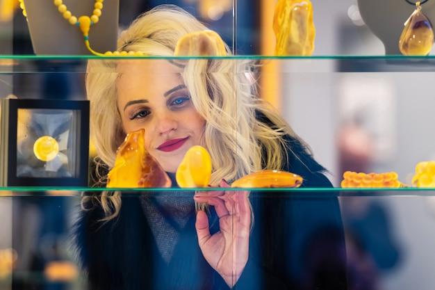 Een jonge, mooie, blonde vrouw kijkt naar barnsteen sieraden in een juwelier. kijk door het raam vanaf de straatkant.