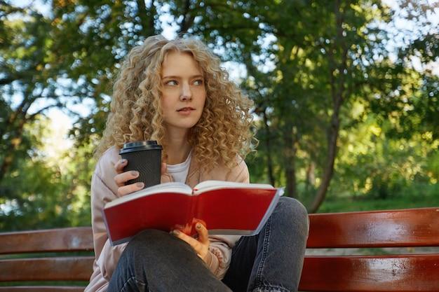 Een jonge mooie blonde vrouw zit met haar benen verscholen op een bankje, met koffie en een notitieboekje