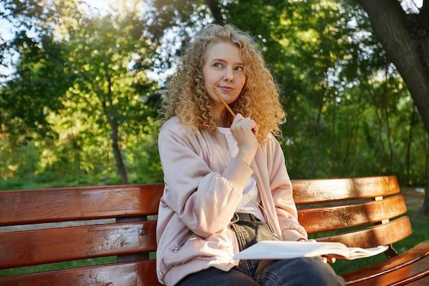 Een jonge mooie blonde vrouw zit op een bankje, met koptelefoon en blocnote, kijkt weg